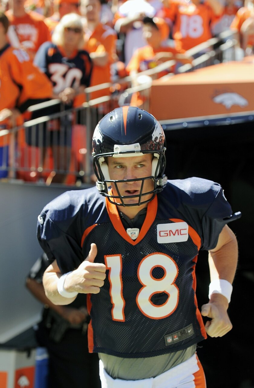 Denver Broncos quarterback Peyton Manning runs onto the field before the start of the NFL Broncos Summer Scrimmage at Sports Authority Field at Mile High on Saturday, Aug. 2, 2014, in Denver. (AP Photo/Chris Schneider)