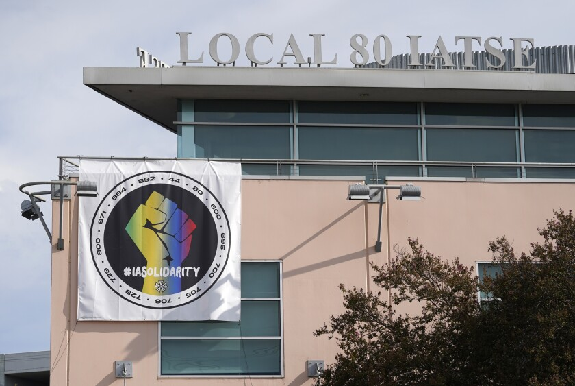 A poster advocating union solidarity hangs from the office building housing The International Alliance of Theatrical Stage Employees Local 80, Monday, Oct. 4, 2021, in Burbank, Calif. The IATSE overwhelmingly voted to authorize a strike for the first time in its 128-year history. (AP Photo/Chris Pizzello)