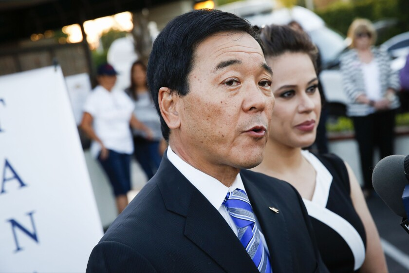 Retired Undersheriff Paul Tanaka, with wife Valerie Tanaka, speaks to reporters while awaiting results of the California primary race for Los Angeles County sheriff.