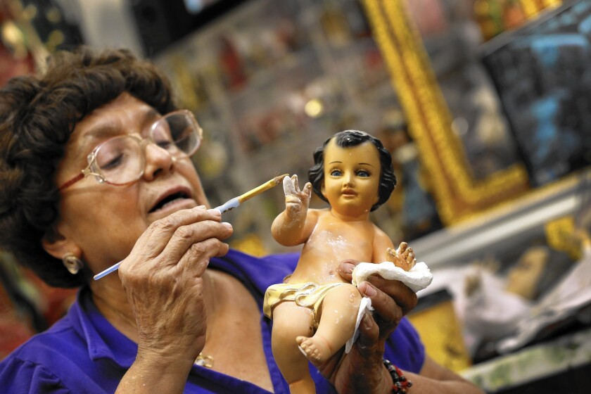Christina Parodi repairs the finger of a baby Jesus that had been chewed by a dog.