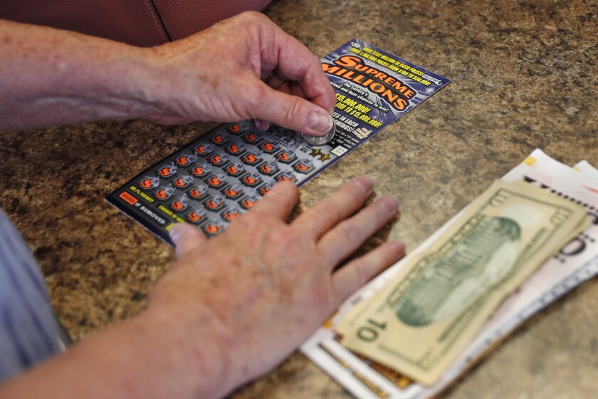 A woman scratches a lottery ticket on June 24 in Methuen, Mass.