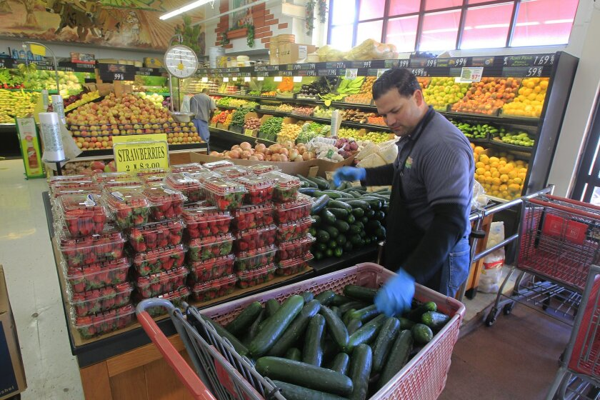 Fernando Kelly sorts produce at the University Avenue store of Super Mercado Murphy's in City Heights.