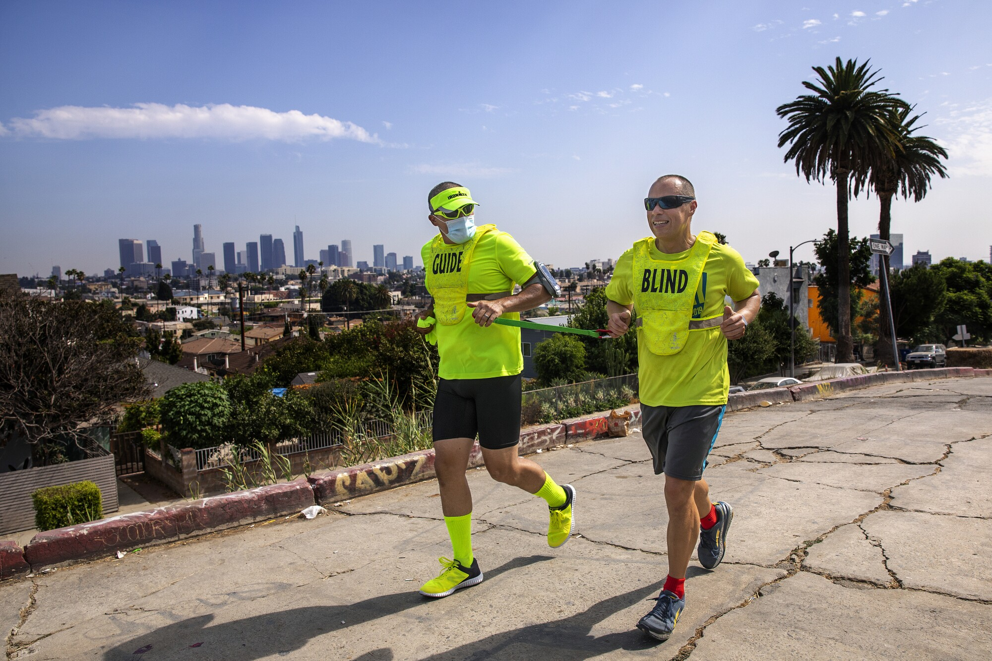 Tony Duenas, right, a marathon runner who is blind, and his guide, Ray Alcanter, jog together on Hoover Street in L.A.
