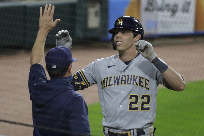Milwaukee Brewers' Christian Yelich, right, celebrates with manager Craig Counsell after hitting an inside-the-park home run against the Chicago White Sox during the fifth inning of a baseball game in Chicago, Thursday, Aug. 6, 2020. (AP Photo/Nam Y. Huh)
