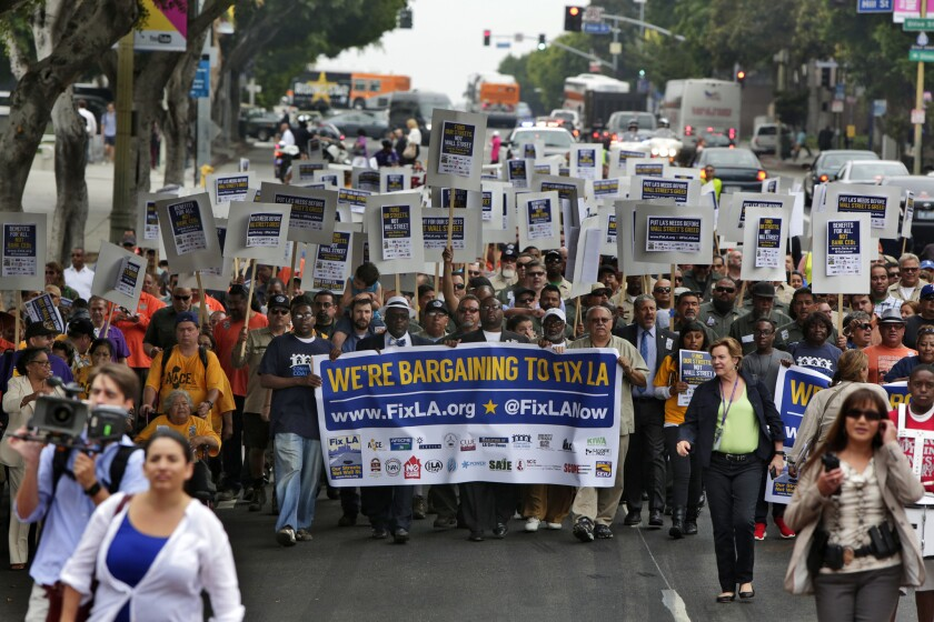 Members of the Fix LA Coalition, which includes labor unions, clergy and community groups, march on their way to City Hall to protest fees the city pays to Wall Street banks in July.