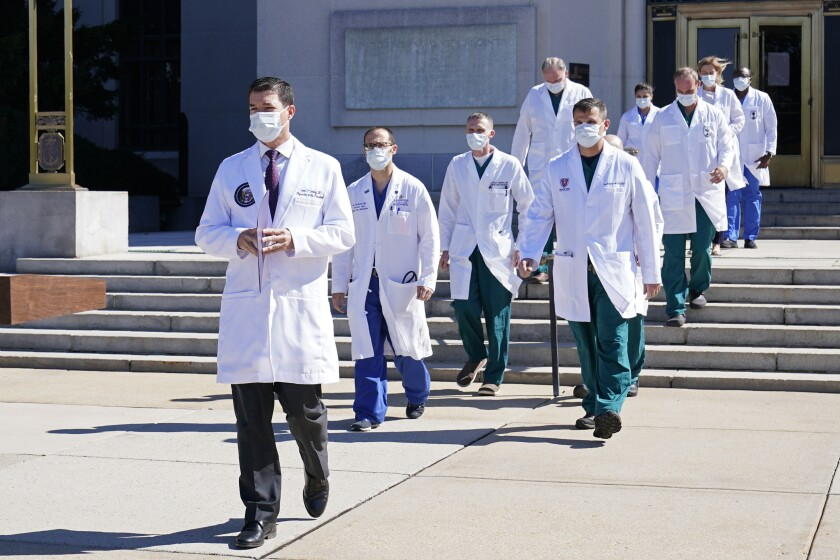 A group of doctors in white coats and masks walk down the steps of Walter Reed Medical Center.