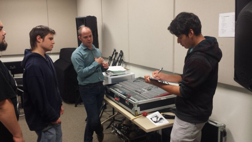 Professor Taylor Smith (center) talks with students Anthony Serrano, Evan Thorn and Carlos Jimenez (left to right) in a music room at Cuyamaca College as they prepare for this Saturday's Coyote Music Festival.