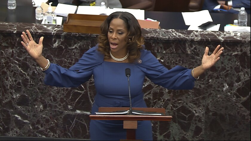House manager Stacey Plaskett speaks and gestures at a Senate lectern