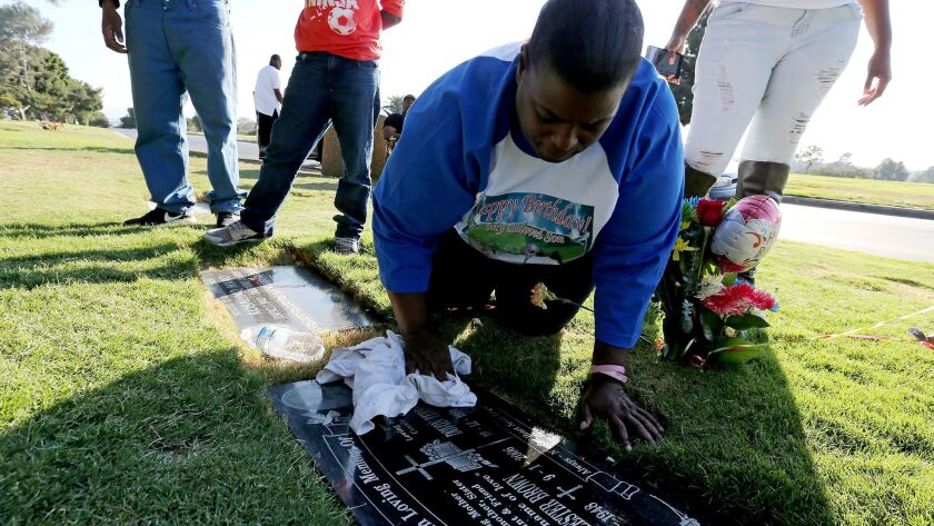 Barbara Pritchett-Hughes cleans the headstone of her son Dovon during a visit to his grave in Inglewood Park Cemetery on what would have been his 25th birthday. Pritchett-Hughes has lost two children to gun violence.