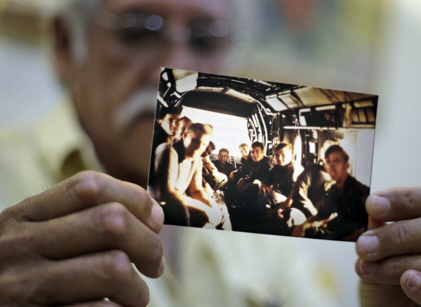 In this Tuesday, April 28, 2015 photo, former U.S. Marines Master Gunnery Sgt. Juan Valdez of Oceanside, California, holds a photo of himself, rear center, sitting on the last helicopter leaving the U.S. Embassy in Saigon on April 30, 1975, in Ho Chi Minh City, Vietnam. On the 40th anniversary of t