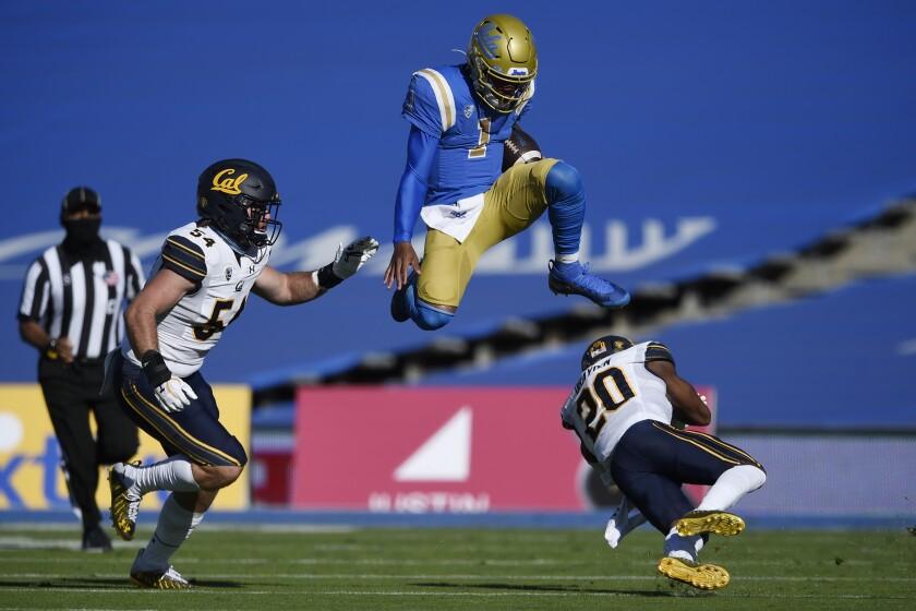 UCLA quarterback Dorian Thompson-Robinson, center, leaps over California cornerback Josh Drayden.