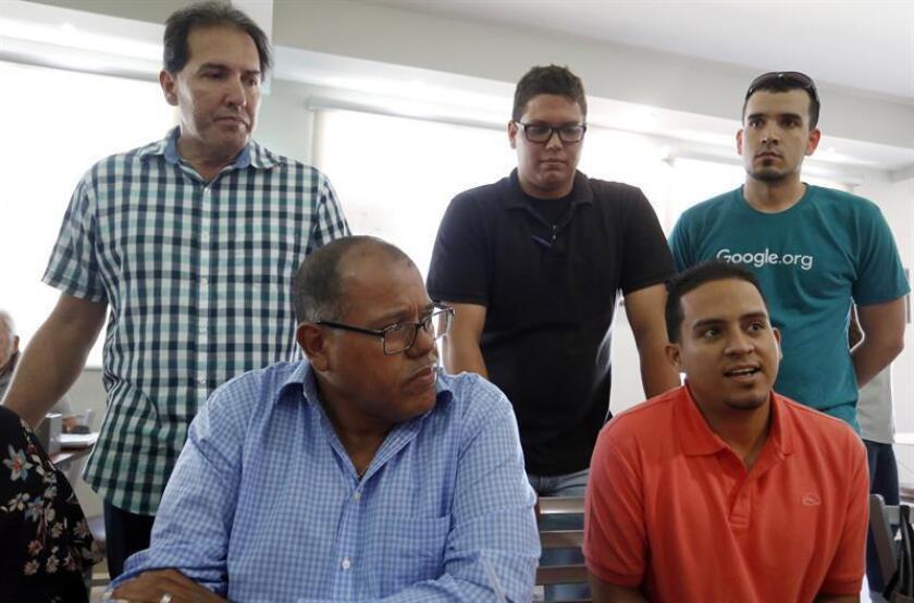 El gerente regional de Google.org, el venezolano Héctor Mujica (d de pie); el empresario Jack Cuardado (c de pie), y Félix Fontanez (i de pie) escuchan a Rey Cintron (i sentado) y Pedro Morales (d sentado), del Programa de Educación Comunal del Entrega y Servicio, (P.E.C.E.S.) el 24 de mayo de 2018, durante una visita de Google a Humacao, Puerto Rico. EFE
