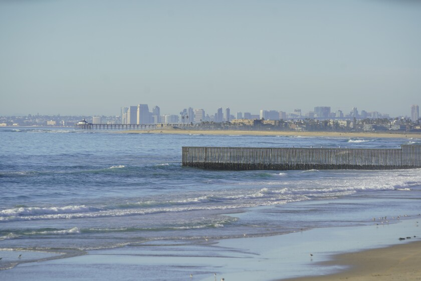 A border fence and San Diego's skyline as seen from Tijuana. The cities together are seeking to be World Design Capital.