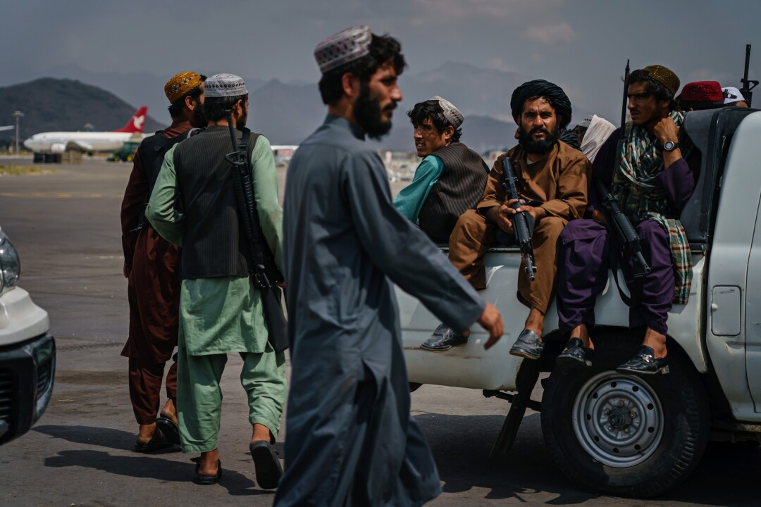 Taliban fighters sit in a pickup truck while others stand next to them