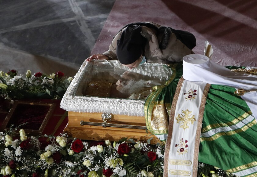 A woman kisses the coffin of Patriarch Irinej as he lies in repose at the St. Sava Temple in Belgrade, Serbia, Saturday, Nov. 21, 2020. Patriarch Irinej, has died after testing positive for the coronavirus. He was 90. (AP Photo/Darko Vojinovic)