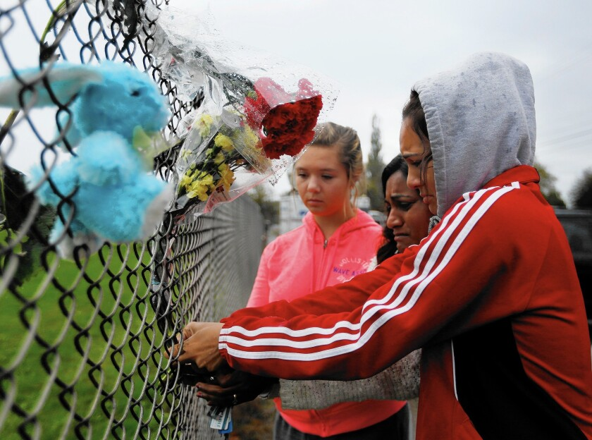 Student Tyanna Davis places flowers on the fence bordering Marysville-Pilchuck High School in Marysville, Wash., the day after another student opened fire, killing one and wounding two before shooting himself to death.