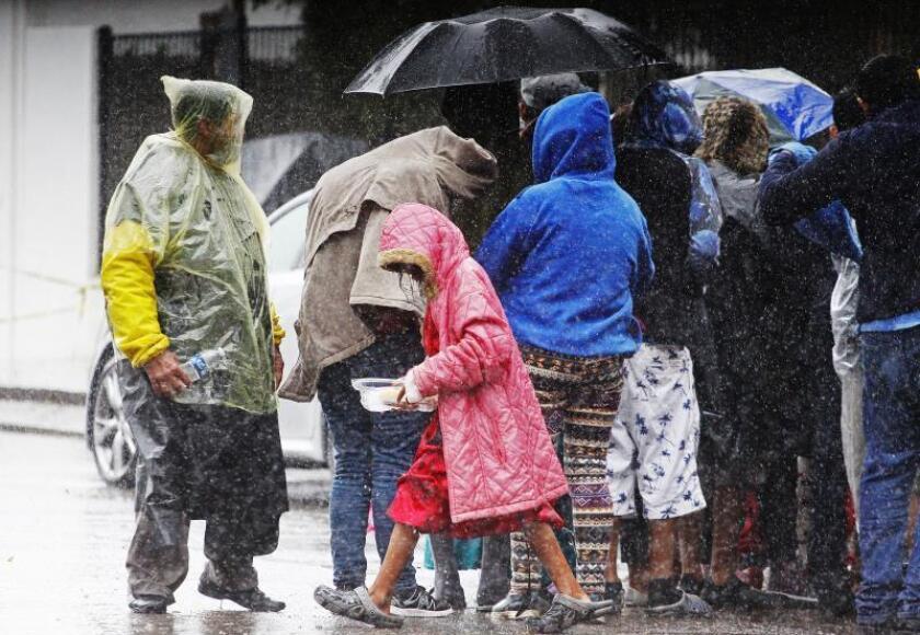 Integrantes de la caravana de migrantes centroamericanos tratan de protegerse luego de que el albergue en el que se concentraban se inundara por las fuertes lluvias hoy en Tijuana (México). La situación de los migrantes centroamericanos estancados en Tijuana entró hoy en un nuevo compás de espera con el comienzo de una huelga de hambre, mientras aguardan la entrada el sábado del nuevo Gobierno mexicano. EFE