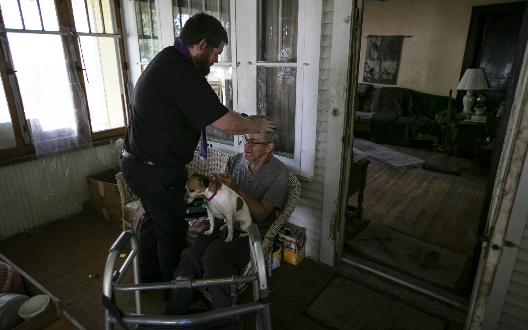 The Rev. Kristopher Cowles blesses Doug Van Loh, 62, at his home as his dog Sadie stands by.