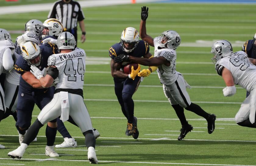 The Chargers' Kalen Ballage runs through a small hole in the Raiders defense at SoFi Stadium.