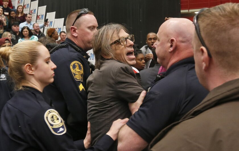 Photojournalist Christopher Morris is escorted by police during the rally of Republican presidential candidate, Donald Trump, Monday, Feb. 29, 2016, at Radford University in Radford, Va. (AP Photo/Steve Helber)