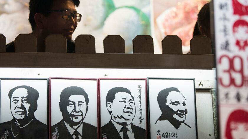 A man stands near a series of paper cuttings depicting Chinese President Xi Jinping next to former C