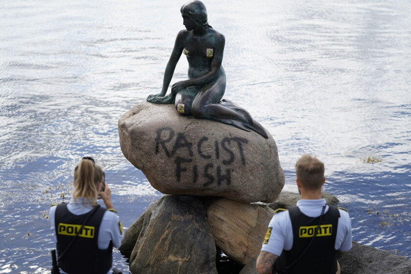 """Police stand by the statue of the Little Mermaid, after it was vandalized, in Copenhagen, Denmark, Friday, July 3, 2020. The famed statue of Hans Christian Andersen's Little Mermaid, one of Copenhagen's biggest tourist draws, has been vandalized ... again. The text """"racist fish"""" was tagged on the stone of which the oft-attacked 1.65-meter (5.4-foot)-high bronze is sitting on at the entrance of the Copenhagen harbour, the Ekstra Bladet daily reported. No one has taken responsibility for the act. (Mads Claus Rasmussen/ Ritzau Scanpix via AP)"""