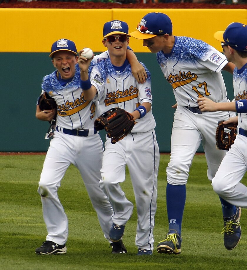 Australia's Myles Chabi, center, celebrates with teammates Lachlan Regan (9), and Blake Cavill (17) after making a diving catch on a line drive by Dominican Republic's Anderson Luciano in right field to save two runs during the fifth inning of an International elimination baseball game at the Little League World Series tournament in South Williamsport, Pa., Saturday, Aug. 22, 2015. (AP Photo/Gene J. Puskar)
