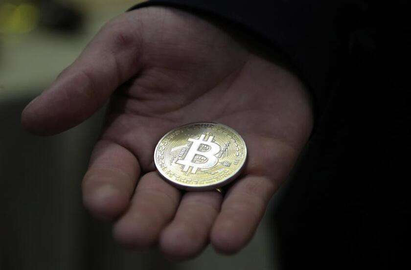 Un visitante sujeta una Bitcoin (moneda virtual) de souvenir durante un seminario impartido en línea por el empresario ruso, activista ortodoxo y fundador del Crypto Cambio CryptoSterlingClub Alisa, German Sterligov. EFE/Archivo
