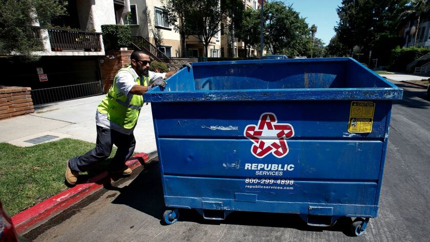 An employee with Athens Services moves a trash bin belonging to a 14-unit condominium building in West L.A. on Aug. 4, 2017.
