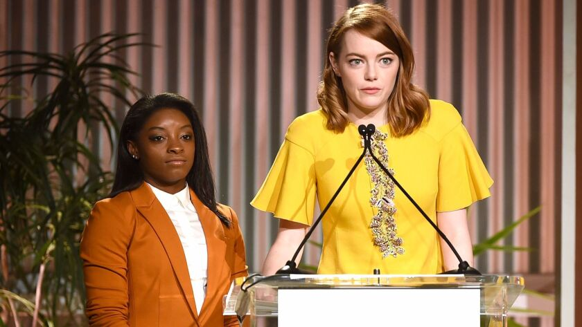Honoree Simone Biles, left, and Emma Stone appear onstage during the Women in Entertainment Breakfast at Milk Studios.