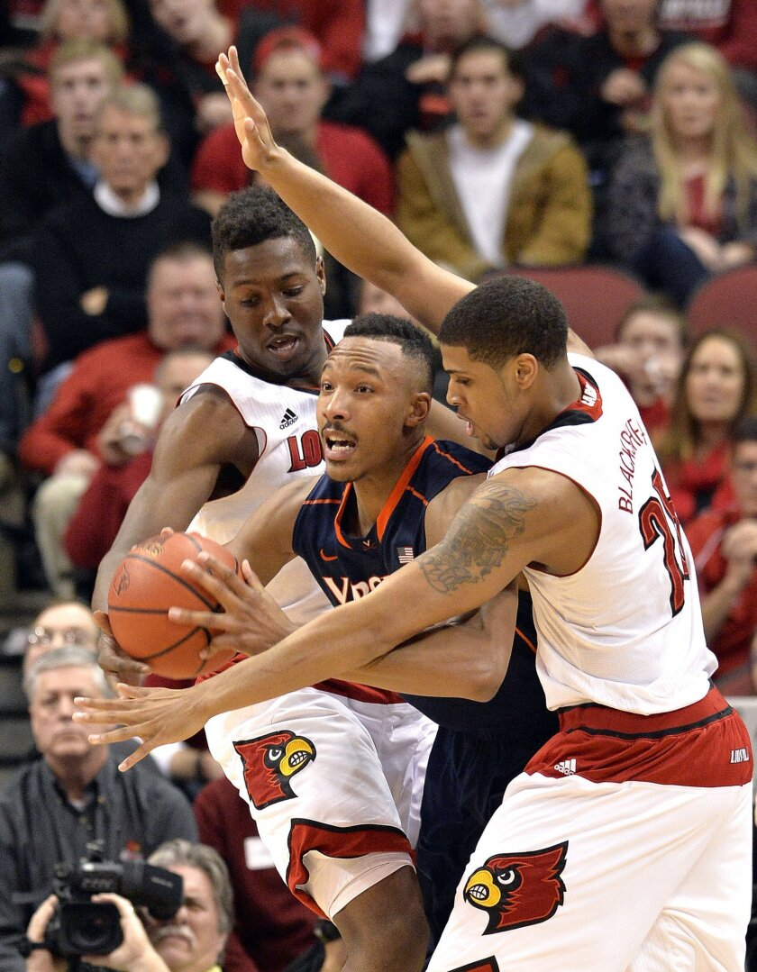 Virginia's Darion Atkins, center, is guarded by Louisville's Chinanu Onuaku, left, and Wayne Blackshear during the second half of an NCAA college basketball game Saturday, March 7, 2015, in Louisville, Ky. Louisville won 59-57. (AP Photo/Timothy D. Easley)