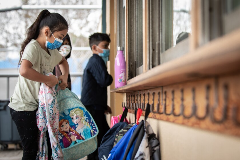 Students at Perkins K-8 in Barrio Logan put their backpacks on hooks on their first day of in-person school Monday.