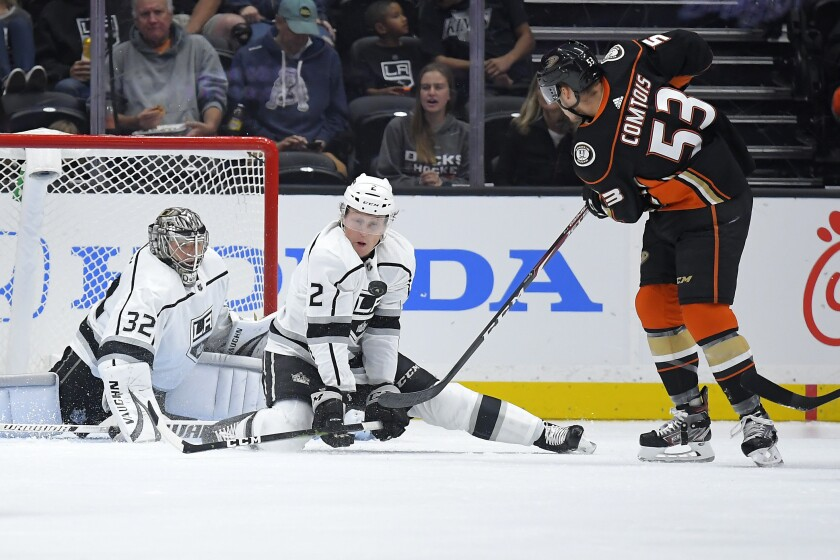 Kings defenseman Paul LaDue, center, stops a shot by Anaheim Ducks left wing Max Comtois in front of goaltender Jonathan Quick.