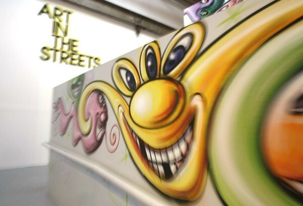 """A portion of """"Spray Paint on Wall"""" by Kenny Scharf marks the entry to the """"Art in the Streets"""" group show at the Geffen Contemporary at the Museum of Contemporary Art in Los Angeles. The MOCA exhibition runs April 17 to Aug. 8."""