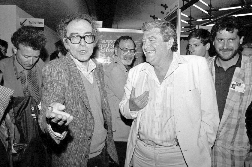 """Director Jean-Luc Godard, left, and Israeli producer Menahem Golan at a news conference in Cannes, France, in May 1987 after the screening of Godard's """"King Lear,"""" which Golan produced."""