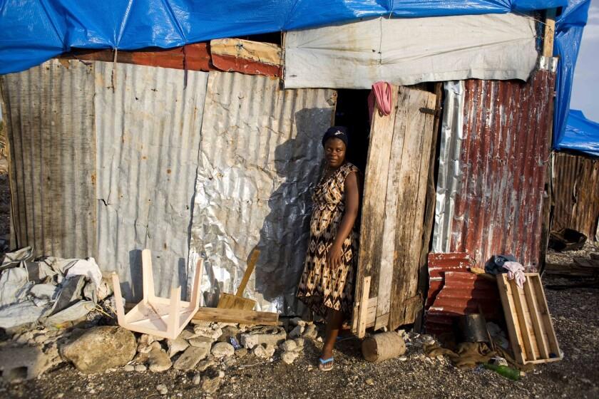 En esta imagen del 31 de octubre de 2016, Nathanaelle Bernard, embarazada de 7 meses, sale del cobertizo donde vive ahora, después de que su casa quedara destruida por el huracán Matthew, en Coteaux, Haití. (AP Foto/Dieu Nalio Chery)
