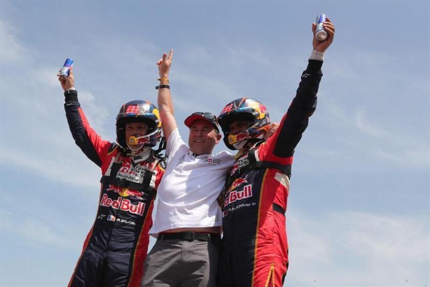 El piloto catarí Nasser Al-Attiyah (d) y su copiloto, el francés Matthieu Baumel (i), celebran junto al director del Toyota Gazoo Razing, Glyn Hall (c), tras ganar el primer lugar en el Rally Dakar 2019, este jueves en Pisco (Perú). EFE