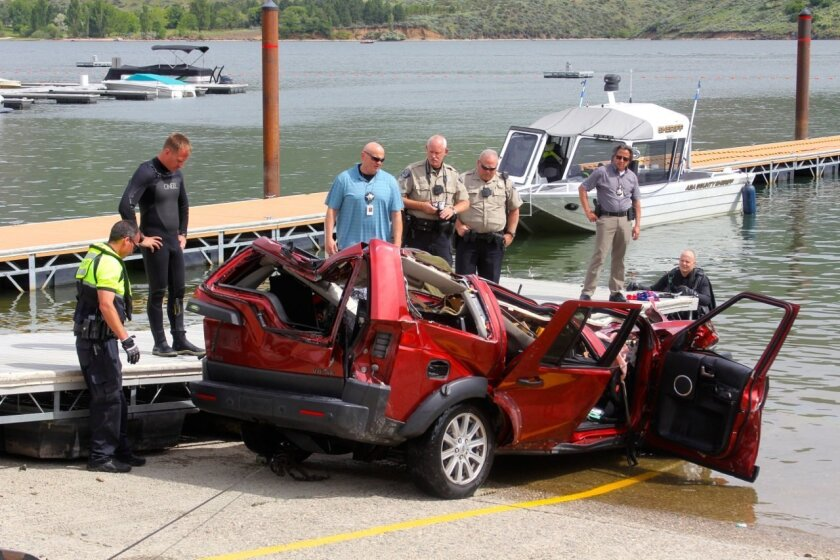 In this photo provided by the Ada County Sheriff's Office, Ada County Sheriff's Deputies and the Boise Fire Department dive team stand by the wreckage of an SUV driven by a 40-year-old Boise woman that plunged off a cliff into the Lucky Peak Reservoir Thursday, June 2, 2016, in Boise, Idaho. Divers