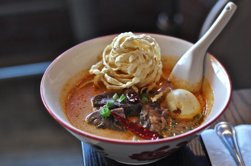 A bowl of khao soi, with long-cooked beef, egg, pickled greens and crispy noodles, at Khao Soi by Inthanon Thai in Hollywood.