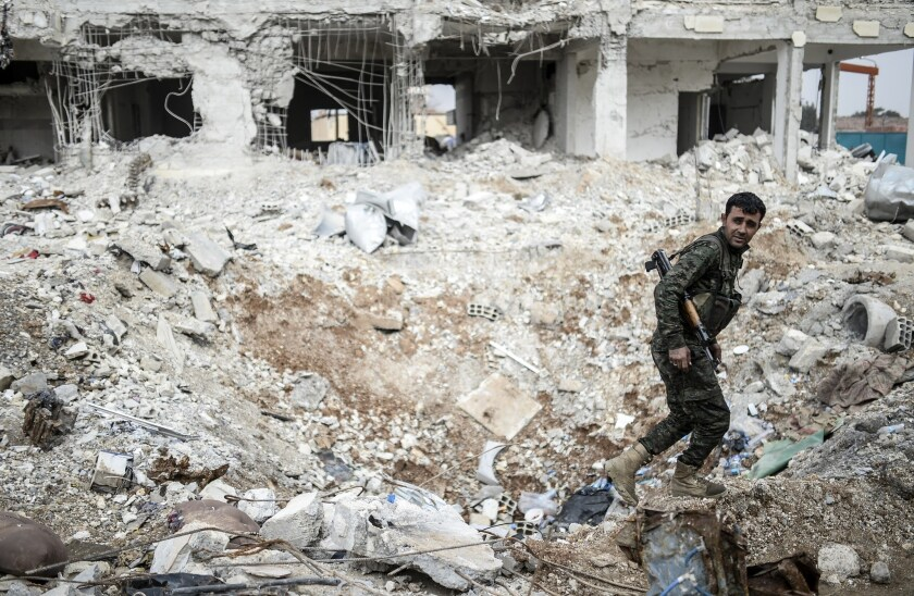 A Kurdish fighter walks through the wreckage of a building in the center of Kobani, Syria, on Jan. 28.