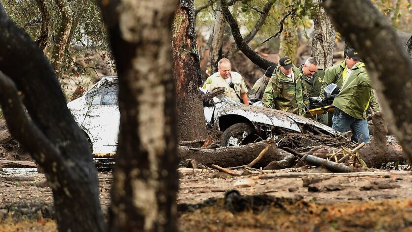 MONTECITO, CALIFORNIA JANUARY 9, 2018-Sheriffs deputies carry a body from the debris near Hot Spring