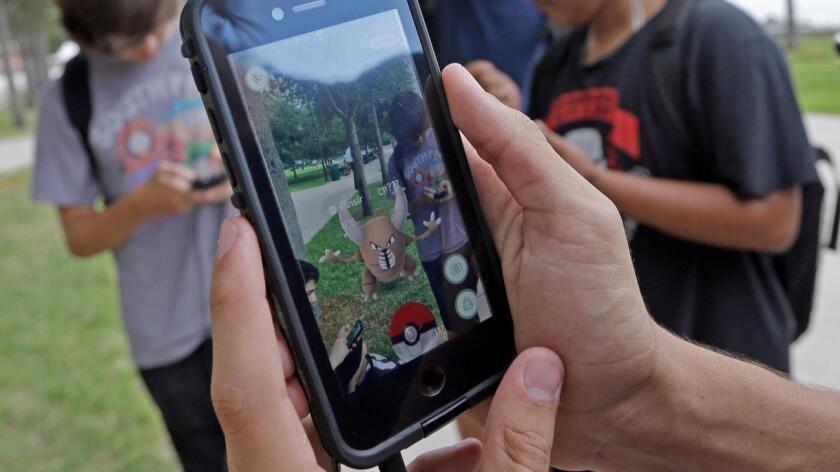 """Un grupo de amigos juegan """"Pokemon Go"""" en el parque Bayfront Park en el centro de Miami. Alan Diaz / Associated Press"""