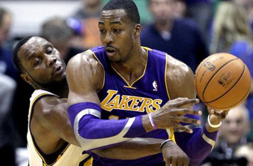 Jazz power forward Paul Millsap knocks the ball from the grasp of Lakers center Dwight Howard in the fourth quarter Wednesday night.