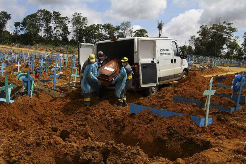 FILE - In this Jan. 6, 2021, file photo, cemetery workers carry the remains of 89-year-old Abilio Ribeiro, who died of the coronavirus, to bury at the Nossa Senhora Aparecida cemetery in Manaus, Amazonas state, Brazil. The global death toll from COVID-19 has topped 2 million. (AP Photo/Edmar Barros, File)