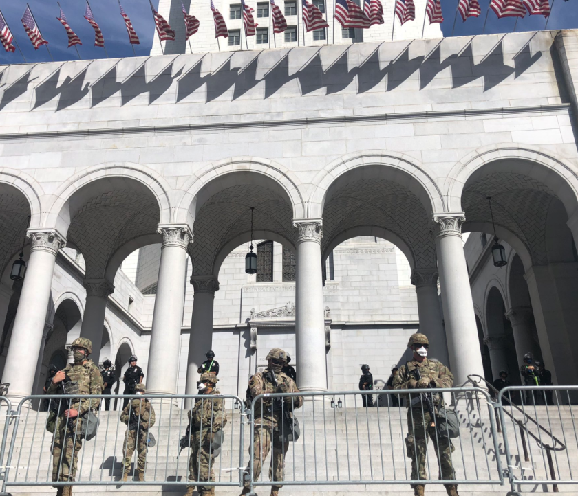 Members of the National Guard help LAPD officers patrol City Hall on Sunday.