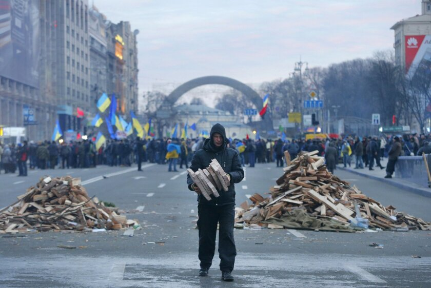 A protester collects firewood for heating in downtown Kiev, Ukraine, early Wednesday, Dec. 4, 2013. Ukraine's opposition failed to force out the government with a parliamentary no-confidence vote Tuesday, leaving political tensions unresolved and a potential standoff between protesters and the country's leaders looming. (AP Photo/Sergei Grits)