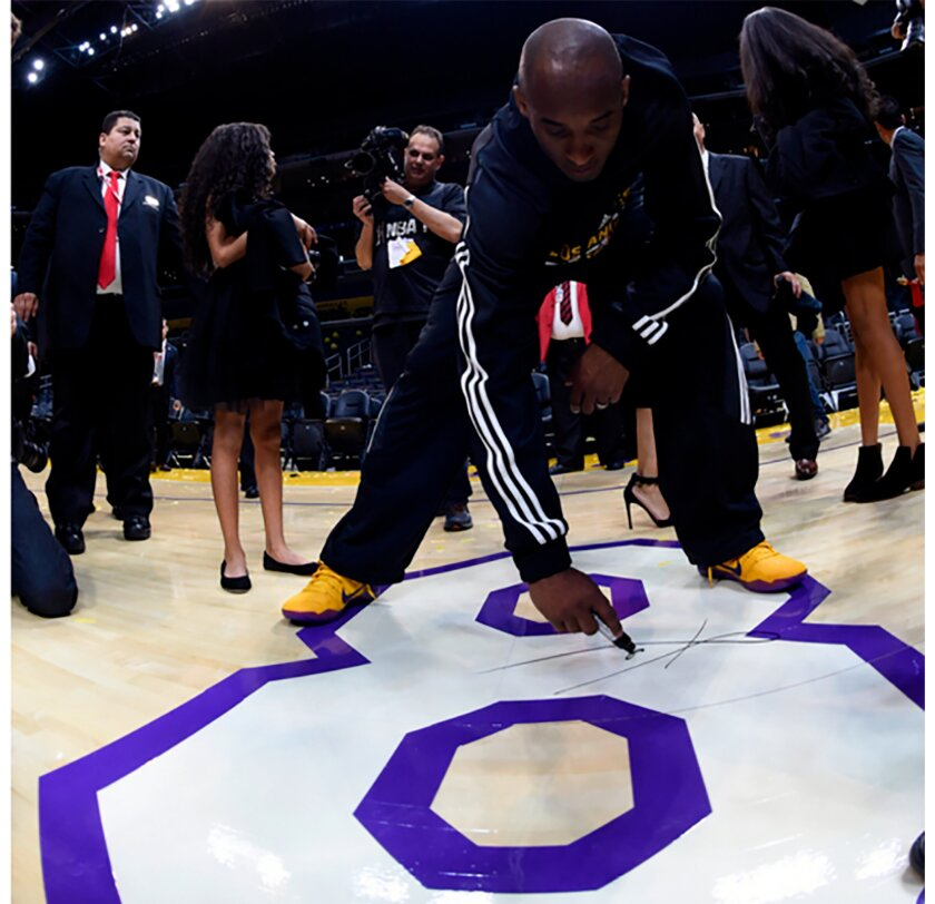 Kobe Bryant signs the No. 8 painted on the Staples Center floor following his final NBA game on April 13, 2016.