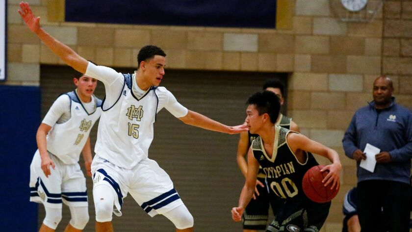 Mater Dei Catholic's Trey Anderson plays defense against Olympian's Cameron Canlapan. Anderson also scored 21 points for the Crusaders.