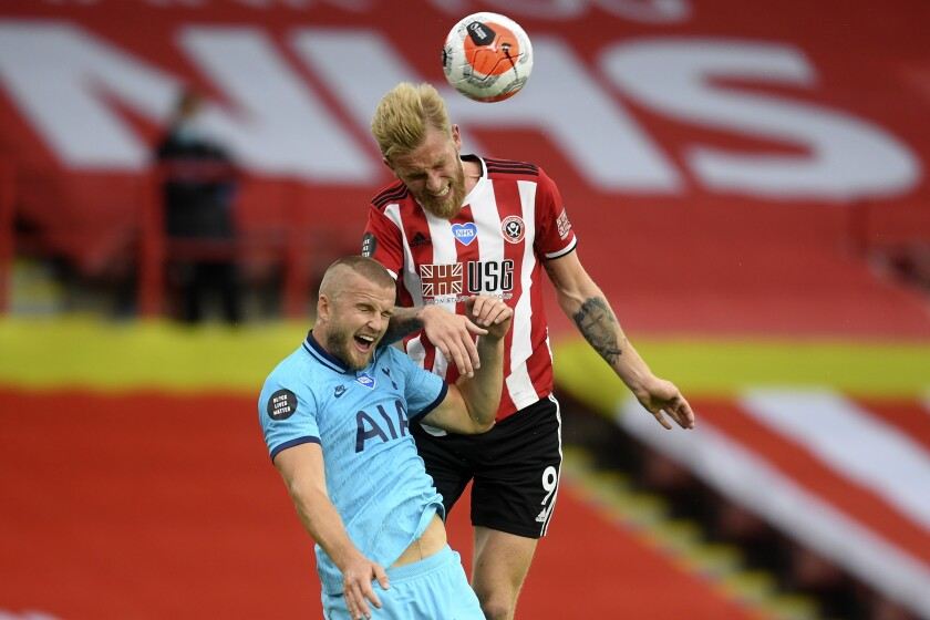 Tottenham's Eric Dier, left, and Sheffield United's Oliver McBurnie jump for the ball during the English Premier League soccer match between Sheffield United and Tottenham Hotspur at Bramall Lane in Sheffield, England, Thursday, July 2, 2020. (Michael Regan/Pool via AP)