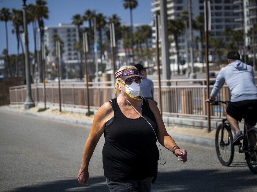 A woman wears a protective mask while exercising on the boardwalk in Huntington Beach